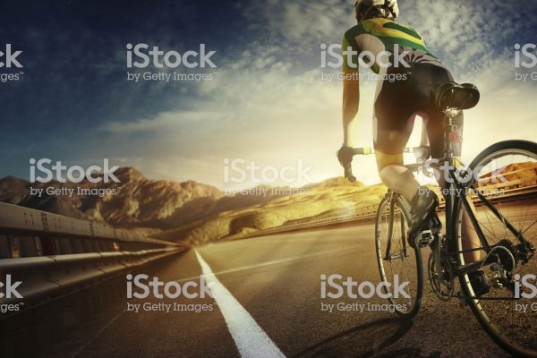 Cyclist riding a bike to the sunset on the highway